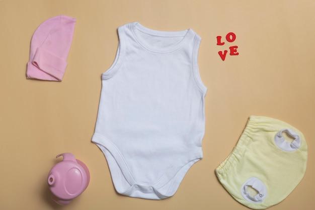Vista superior em close-up. maquete de macacão branco em branco, calcinha de recém-nascido amarela em fundo bege, com espaço de cópia - modelo de maquete de roupas de bebê perfeito