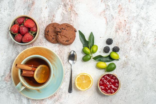 Vista superior em close-up morangos morangos chocolate cookies frutas cítricas romã colher de limão uma xícara de chá com limão na mesa