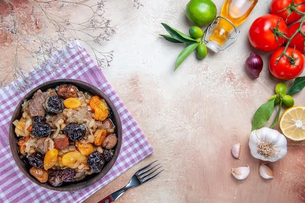 Vista superior em close-up pilaf pilaf com frutas secas na toalha de mesa tomate alho óleo limão garfo