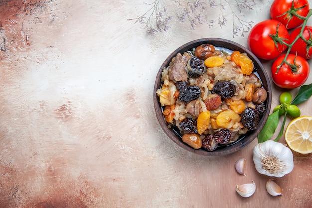 Vista superior em close-up pilaf tigela de arroz, castanhas, frutas secas, tomate, alho, limão