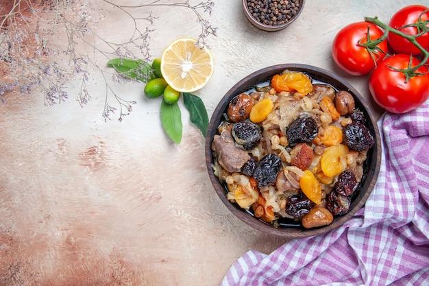 Vista superior em close-up pilaf um apetitoso arroz frutas secas pimenta preta toalha de mesa tomates