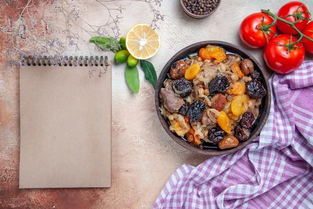 Vista superior em close-up pilaf, um apetitoso arroz, frutas secas, pimenta preta, tomates, creme, caderno