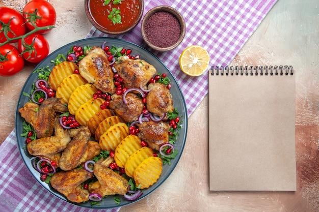 Vista superior em close-up prato asas de frango batatas tomate molho especiarias no caderno de toalha de mesa