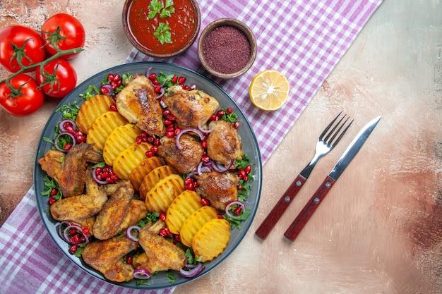 Vista superior em close-up prato asas de frango batatas tomates molho especiarias na faca de garfo toalha