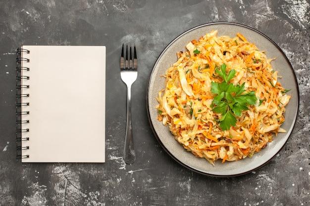 Vista superior em close-up prato branco de repolho com repolho, cenoura, ervas, garfo, caderno branco