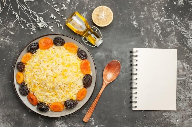 Vista superior em close-up prato de arroz com arroz e frutas secas, colher de limão, caderno de óleo