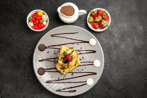 Vista superior em close-up prato de bolo de doces com chocolate e morangos ao lado das tigelas de doces de morangos e calda de chocolate
