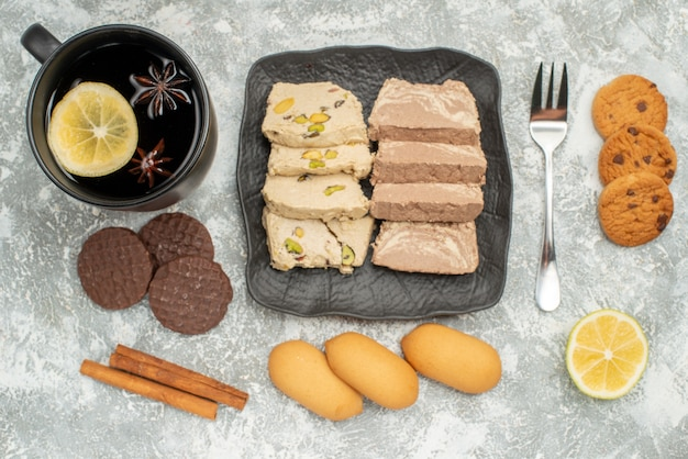 Vista superior em close-up prato de doces com biscoitos halva de semente de girassol e garfo de canela uma xícara de chá