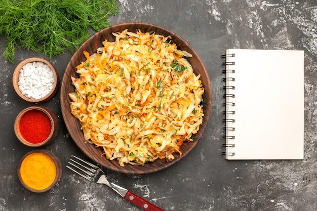 Vista superior em close-up prato de ervas de repolho prato de repolho garfo caderno taças de especiarias coloridas