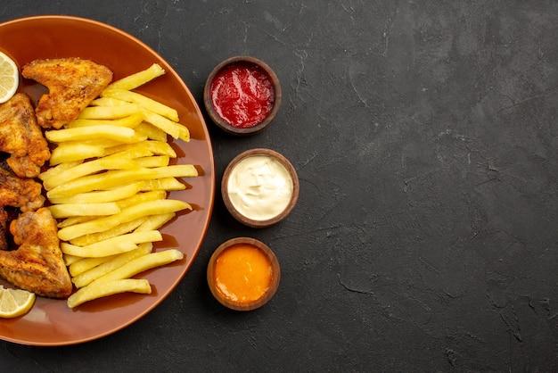 Vista superior em close-up prato de fastfood com batatas fritas, asas de frango e limão e três tigelas de diferentes tipos de molhos na mesa escura