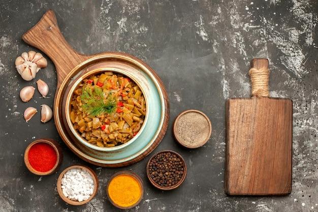 Vista superior em close-up prato de feijão verde do feijão verde com tomate na placa de madeira cinco tipos de especiarias placa de corte e alho na mesa escura