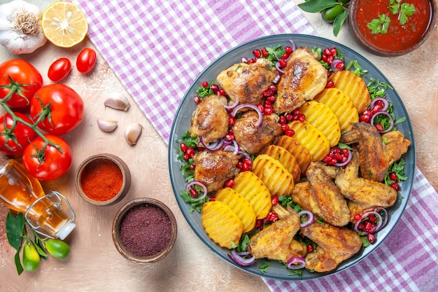 Vista superior em close-up prato de frango com asas de frango, batata, limão, óleo, alho, tomate, especiarias