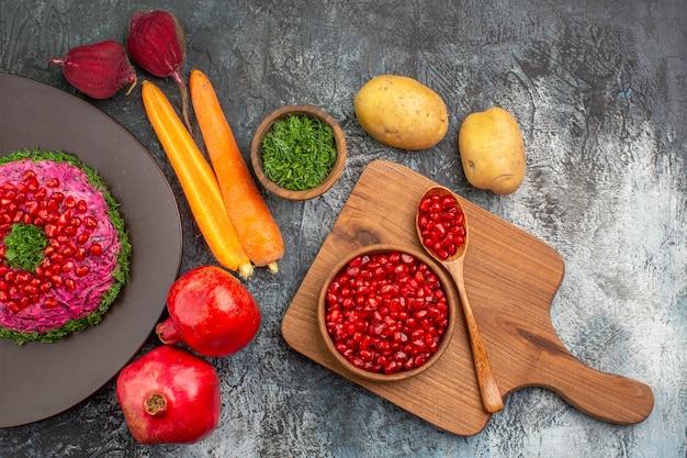 Vista superior em close-up prato de natal com romãs no tabuleiro com sementes de romã vegetais