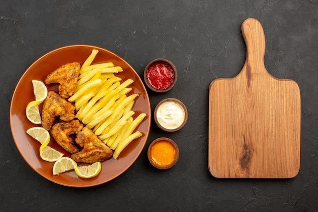 Vista superior em close-up prato fastfood de asas de frango, batata frita e limão ao lado de tigelas de três tipos de molhos e tábua de cozinha de madeira na mesa