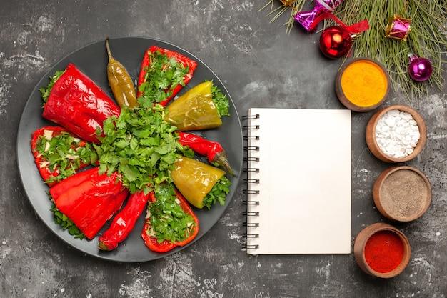Vista superior em close-up prato pimentas com ervas especiarias coloridas, árvore de natal, brinquedos, caderno branco