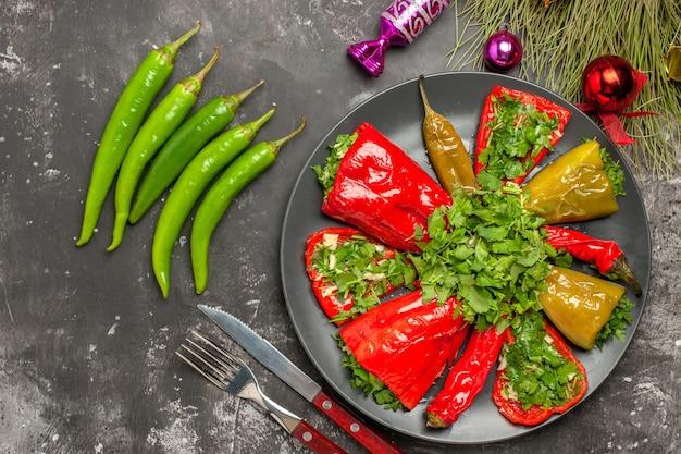 Vista superior em close-up prato pimentas com ervas faca garfo bombons pimenta brinquedos de natal