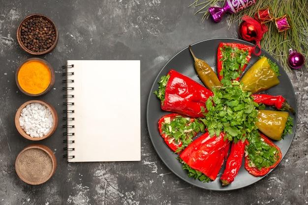 Vista superior em close-up prato pimentas no prato caderno branco especiarias brinquedos para árvores de natal