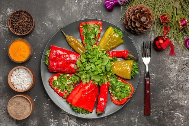 Vista superior em close-up prato pimentas no prato garfo especiarias brinquedos para árvores de natal
