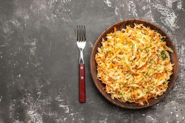 Vista superior em close-up repolho com cenoura o apetitoso repolho de ervas de cenoura no garfo do prato