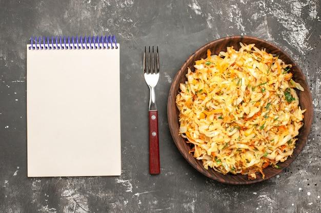 Vista superior em close-up repolho com cenouras o apetitoso garfo de caderno de repolho com ervas de cenoura