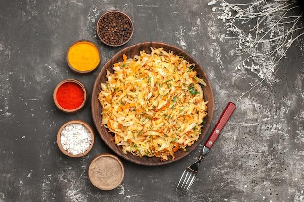 Vista superior em close-up repolho com prato de cenoura de ervas de cenoura repolho garfo tigelas de especiarias