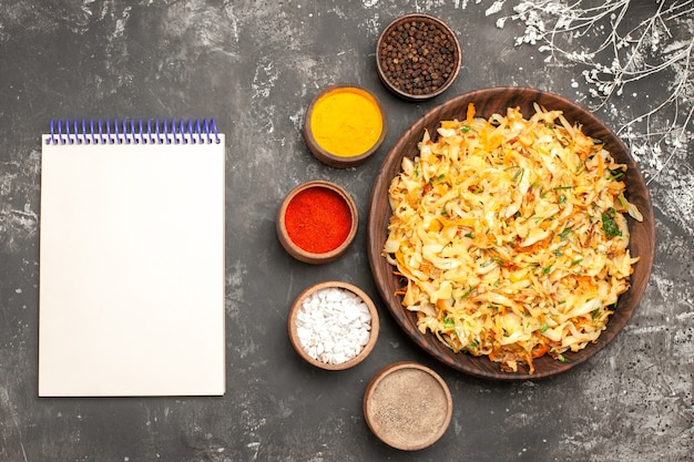 Vista superior em close-up repolho com prato de cenoura de repolho caderno branco tigelas de especiarias
