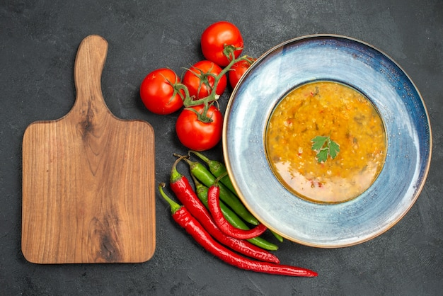 Vista superior em close-up sopa de lentilha sopa de lentilha pimentas tomates com pedicelos na tábua de corte