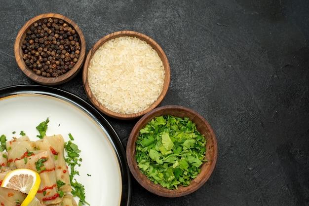 Vista superior em close-up temperos e molhos prato branco de repolho recheado com ervas, molho vermelho e limão ao lado de tigelas de ervas de arroz e pimenta preta no lado esquerdo da superfície escura
