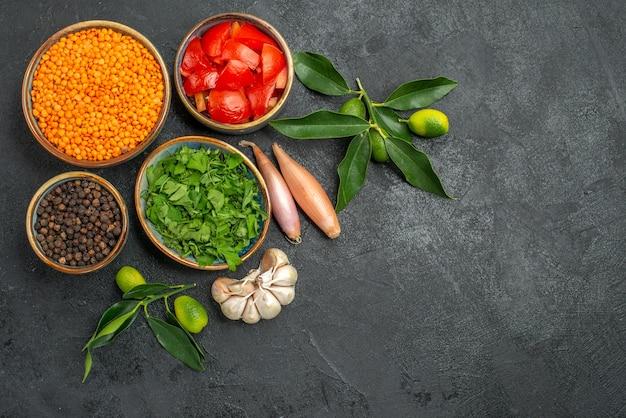 Vista superior em close-up temperos tigelas de tomate pimenta preta lentilha ervas cebola alho