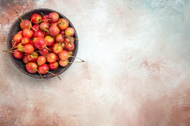 Vista superior em close-up tigela de cerejas na mesa rosa-branco-cinza