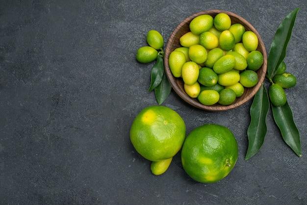 Vista superior em close-up tigela de frutas cítricas com tangerinas de folhas