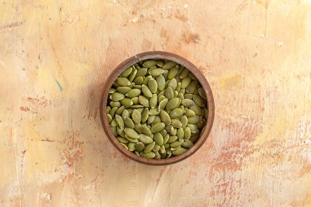 Vista superior em close-up tigela de sementes de abóbora descascadas na mesa