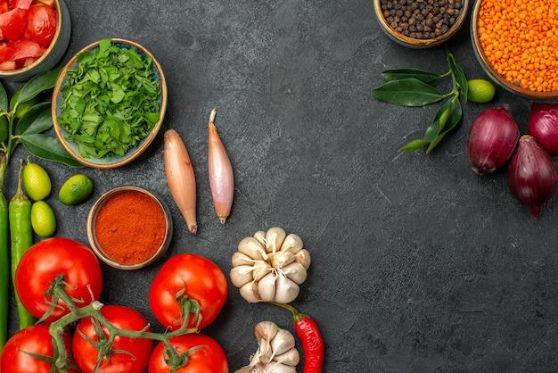 Vista superior em close-up tomate tigela de lentilha cebola pimenta preta tomate pimenta pimenta especiarias ervas