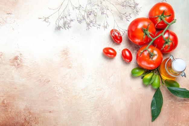 Vista superior em close-up tomates tomates com pedicelos frutas cítricas com folhas garrafa de óleo