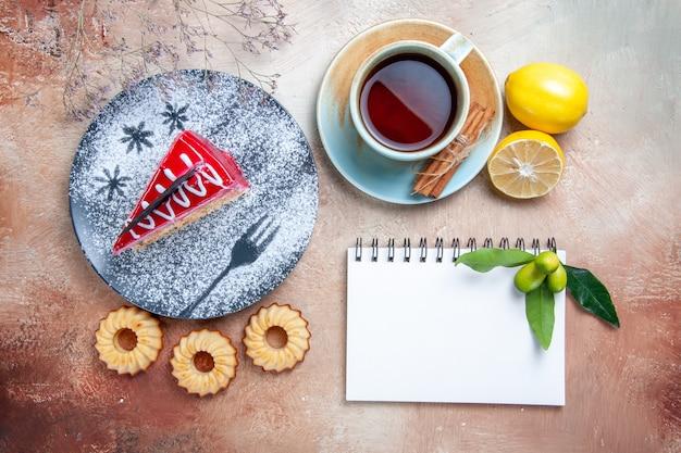 Vista superior em close-up um bolo um bolo biscoitos uma xícara de chá canela limão branco caderno
