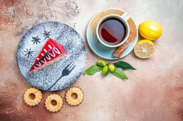 Vista superior em close-up um bolo um bolo biscoitos uma xícara de chá canela limão