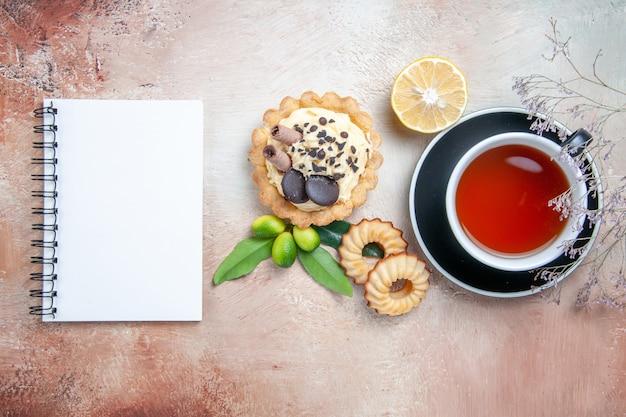 Vista superior em close-up uma xícara de biscoitos de cupcake de chá uma xícara de chá de frutas cítricas caderno branco