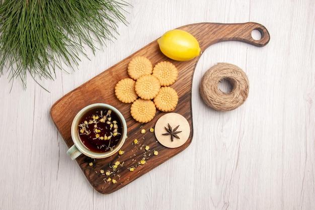 Vista superior em close-up uma xícara de chá uma xícara de biscoitos de chá de ervas, limão, anis estrelado na placa de madeira ao lado dos galhos da árvore de natal