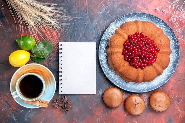 Vista superior em close-up uma xícara de chá, uma xícara de chá, caderno branco, bolo, cupcakes, com, bagas, limões