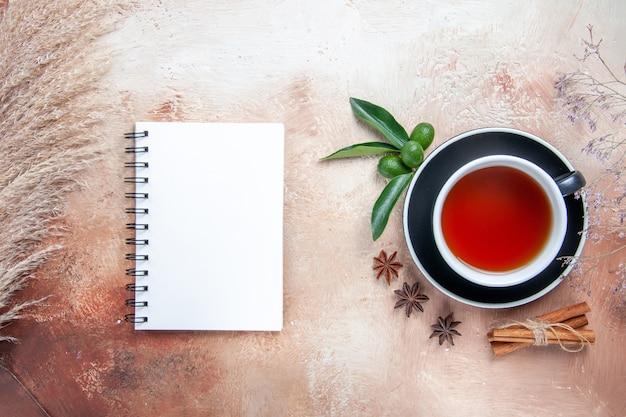 Vista superior em close-up uma xícara de chá uma xícara de chá canela em pau frutas cítricas caderno branco