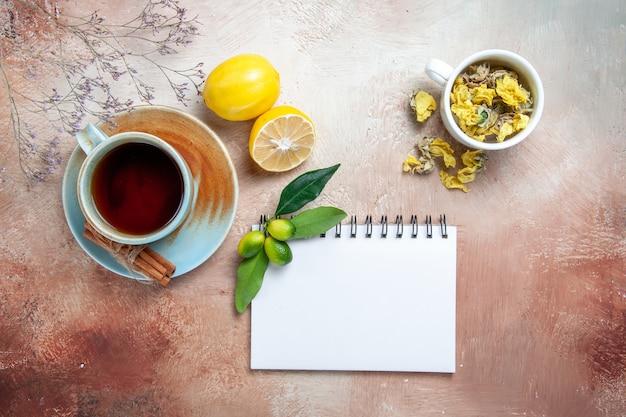 Vista superior em close-up uma xícara de chá uma xícara de chá canela limão branco caderno ervas