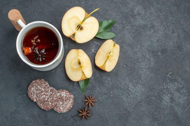 Vista superior em close-up uma xícara de chá uma xícara de chá com biscoitos de canela e fatias de maçã