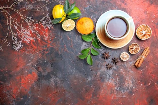 Vista superior em close-up uma xícara de chá uma xícara de cupcake de chá preto limão, anis estrelado, canela, ramos