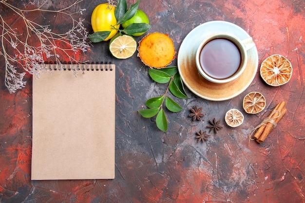 Vista superior em close-up uma xícara de cupcake de chá uma xícara de chá preto limão anis estrelado caderno canela