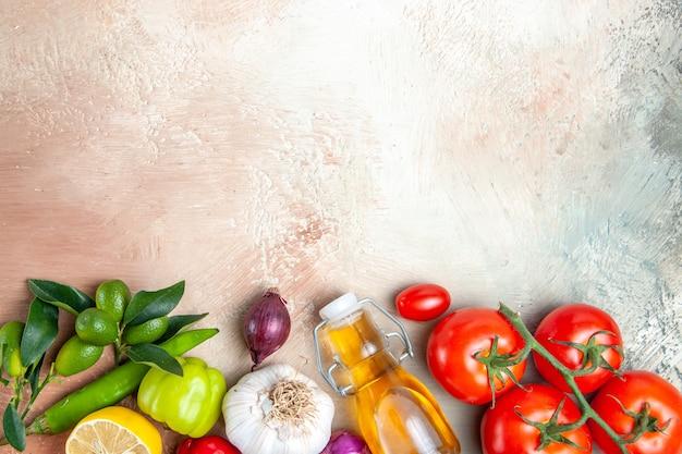 Vista superior em close-up vegetais alho pimentões limão óleo cebola tomates com pedicelos