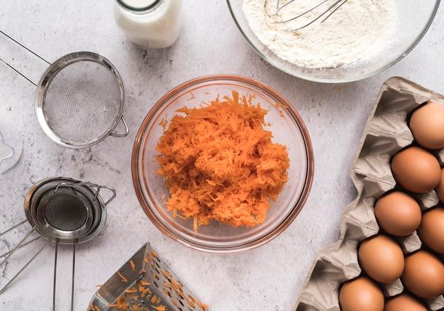 Vista superior em cubos de cenoura em uma tigela, rodeada de ovos