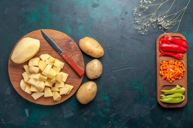 Vista superior em fatias de batatas frescas com pimentas fatiadas no fundo azul escuro