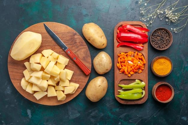 Vista superior em fatias de batatas frescas com temperos e pimentões fatiados em fundo azul escuro