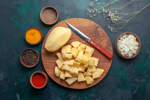 Vista superior em fatias de batatas frescas com temperos no fundo azul escuro
