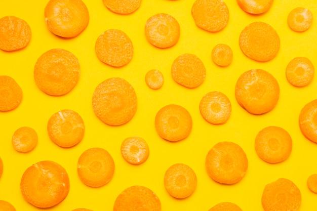 Vista superior em fatias de cenoura em fundo amarelo